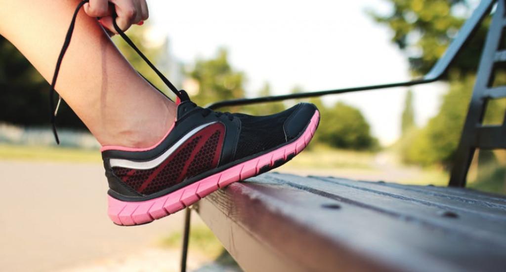 pige som binder sine snørebånd inden hun skal ud at løbe