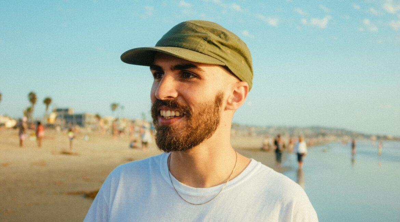 Mand står på strand og smiler